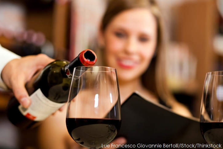 Woman watching red wine be poured into a glass