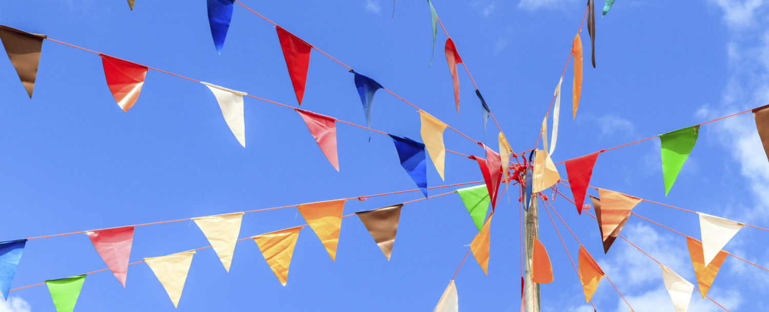 Festival Flags with blue sky dotted with clouds beyond it