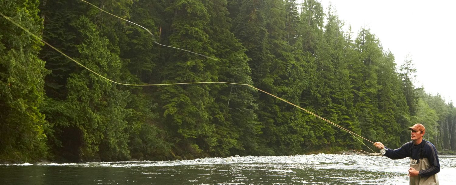 Lone man fly fishing in waders in a river with a forest in the background