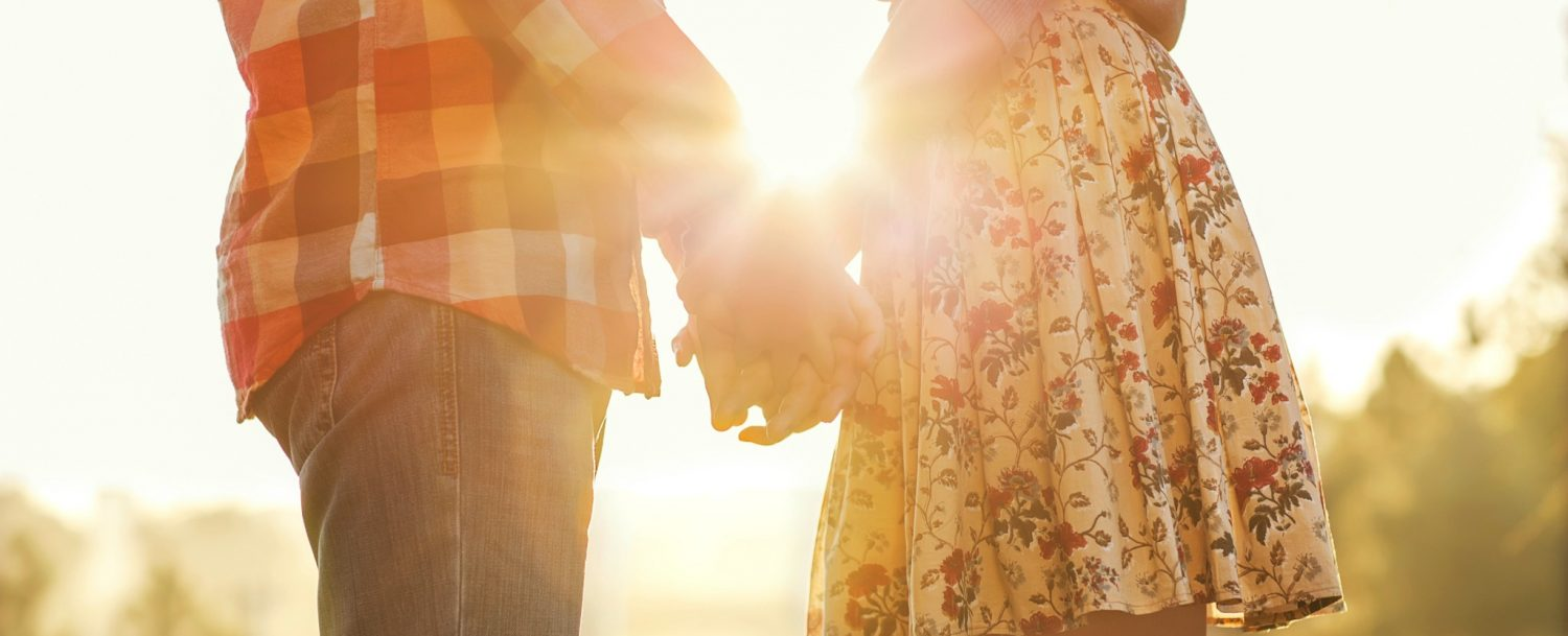 Couple Holding Hands with sunlight streaming through their arms