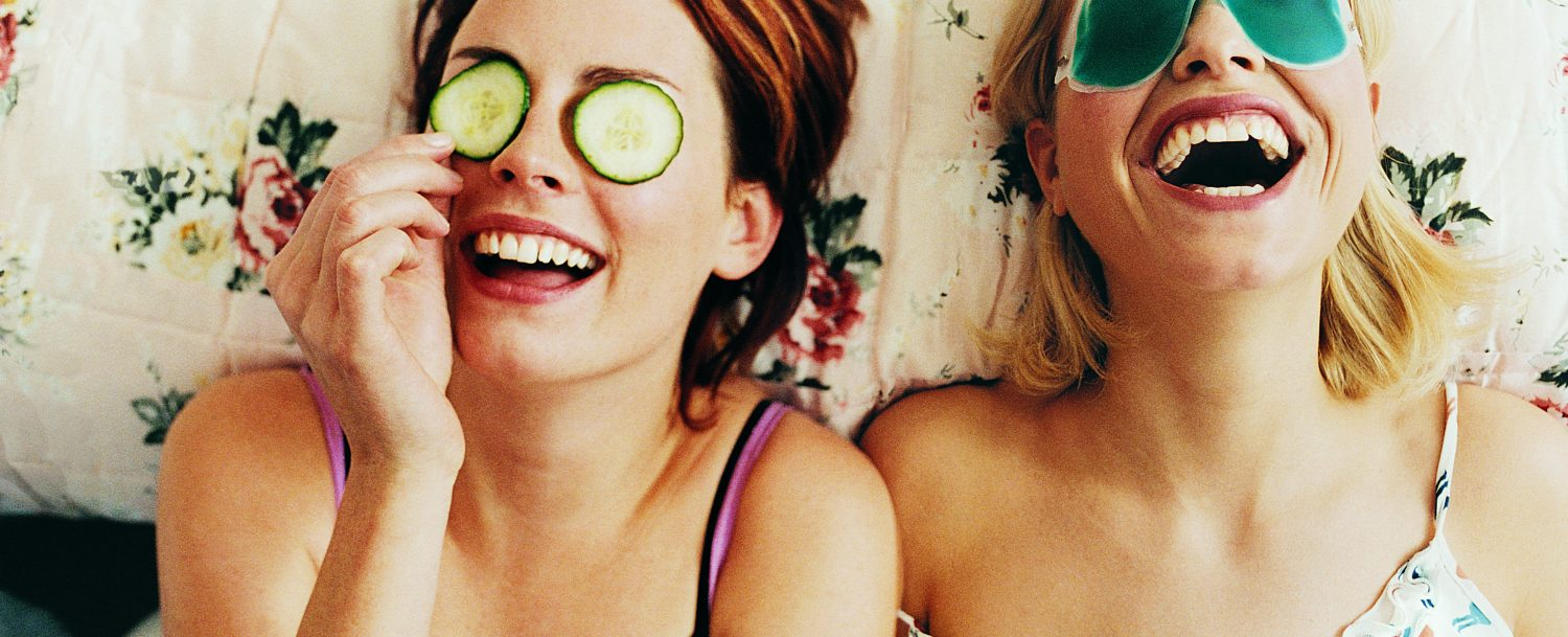 Two Women Lying in Bed Wearing Eye Masks