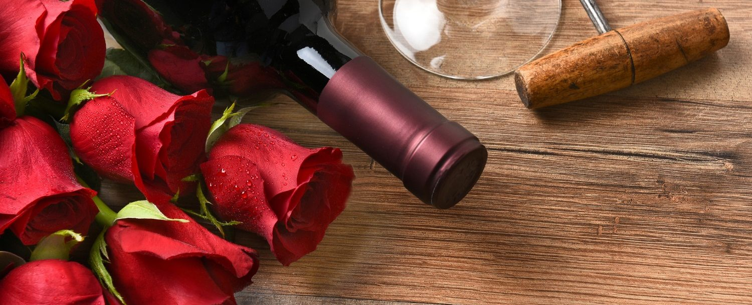 Wine and Roses for a Valentine's Day in Northern Virginia | A wine bottle with red roses and a glass and cork screw on a rustic wood table.